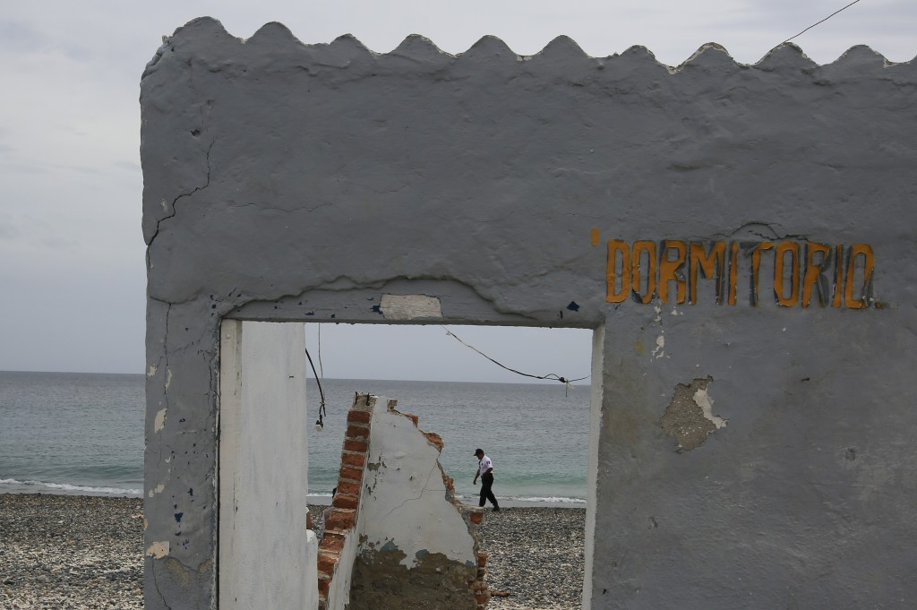 "A prison guard walks on a beach past a dilapidated structure with the Spanish sign: Bedroom,"" during a media tour of the now closed Islas Marias penal"
