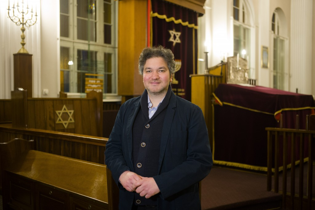 This Wednesday, March 20, 2019 photo Jonathan Marcus a German member of 'Fraenkelufer' synagogue poses for a photo inside the prayer room of the so-ca...