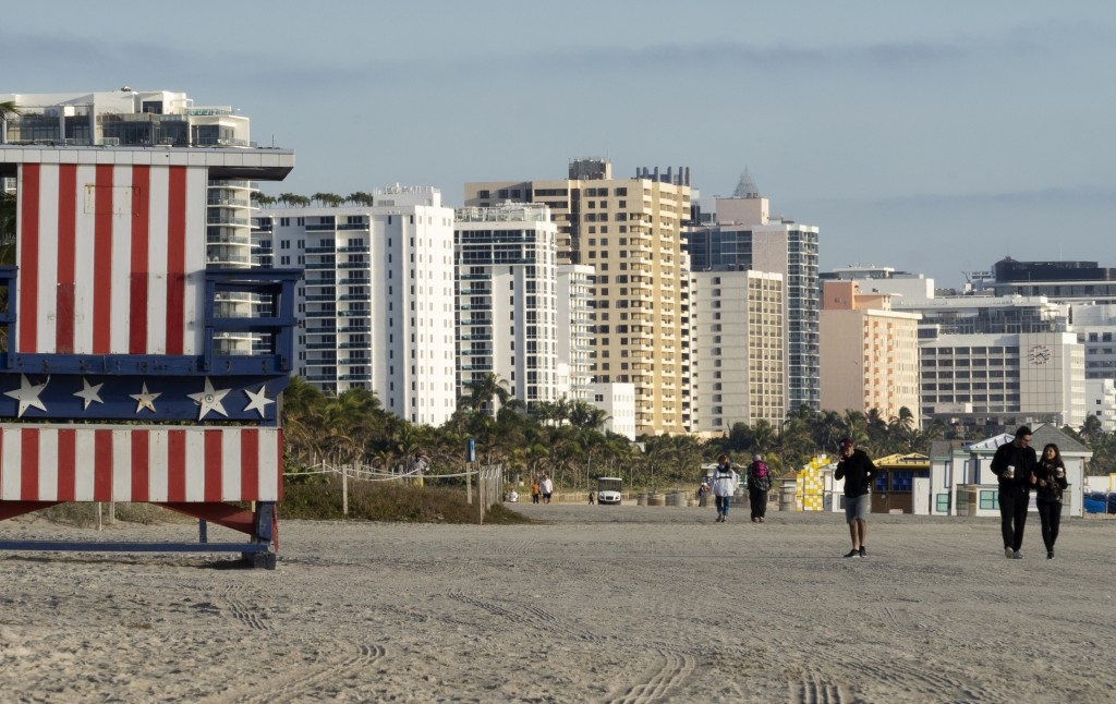 In this photo taken on Jan. 21, 2019, people walk past a lifeguard booth painted in the colors of an American flag on a beach in Miami Beach, Fla. The...