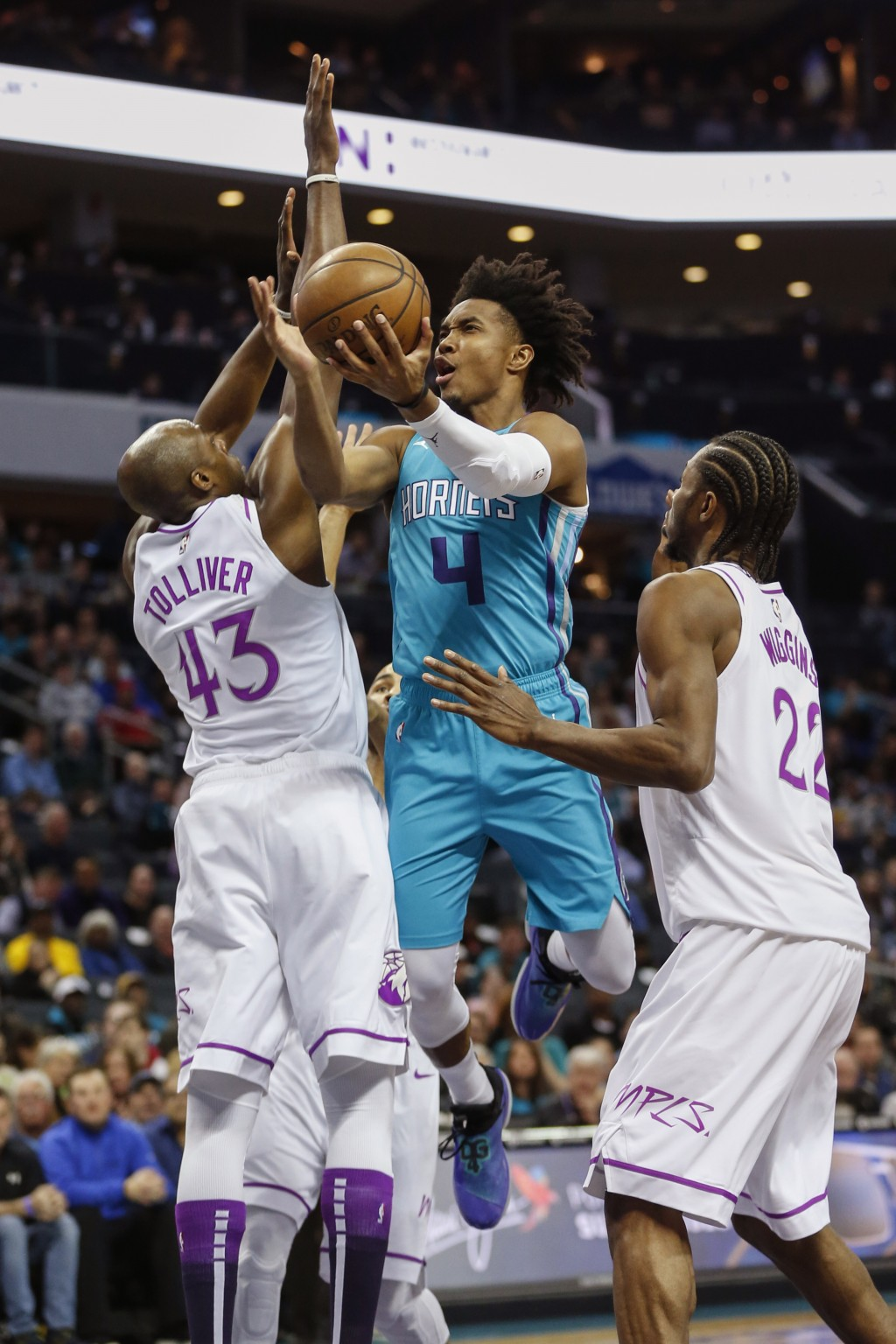 Charlotte Hornets guard Devonte' Graham (4) drives between Minnesota Timberwolves forwards Anthony Tolliver, left, and Andrew Wiggins (22) in the firs