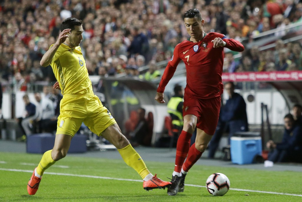 Portugal's Cristiano Ronaldo, right, dribbles past Ukraine's Taras Stepanenko during the Euro 2020 group B qualifying soccer match between Portugal an...