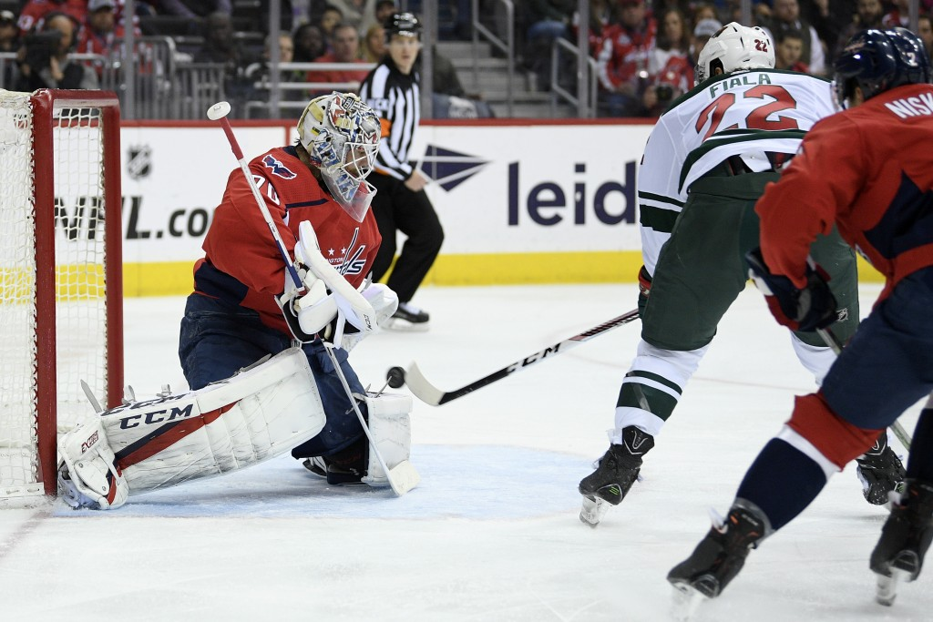 Minnesota Wild left wing Kevin Fiala (22) shoots against Washington Capitals goaltender Braden Holtby (70) during the first period of an NHL hockey ga...