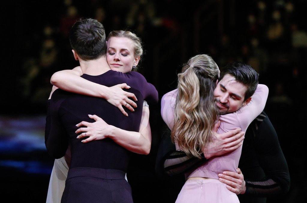 Gabriella Papadakis and Guillaume Cizeron of France, back to camera, hug Madison Hubbell and Zachary Donohue of the U.S. during the medal ceremony for