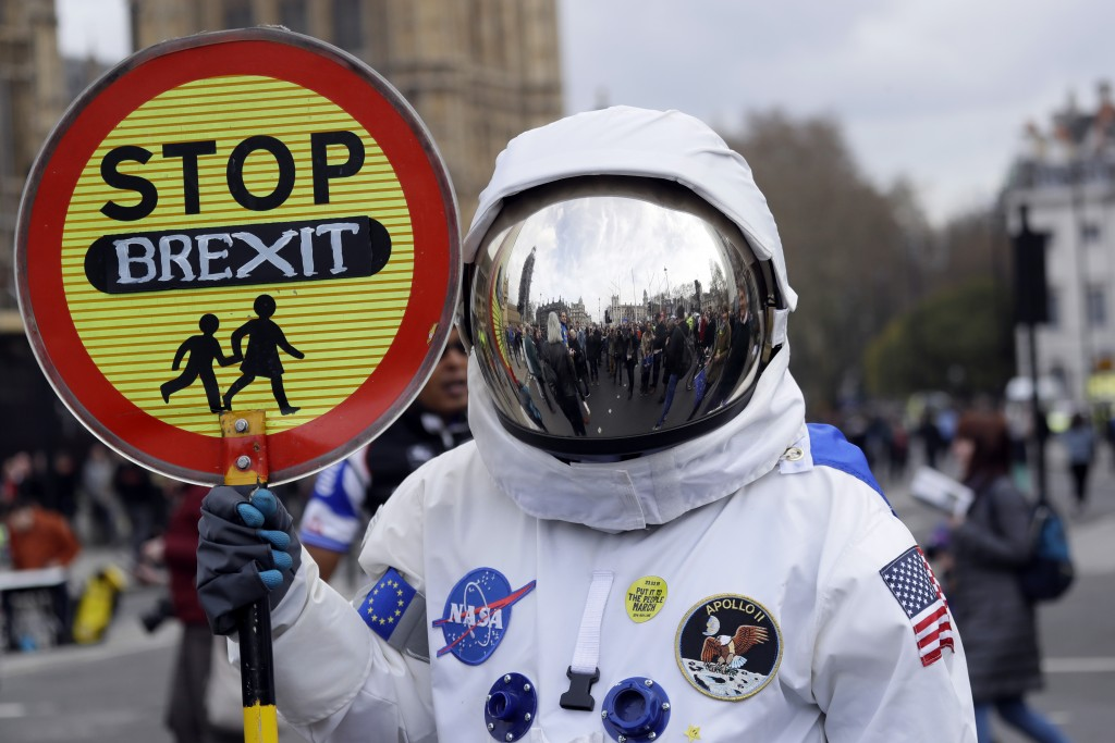 A demonstrator in an astronaut suit carries a sign during a Peoples Vote anti-Brexit march in London, Saturday, March 23, 2019. The march, organized b