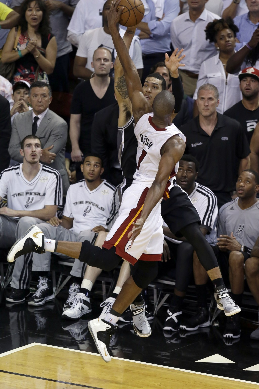FILE - In this June 19, 2013, file photo, Miami Heat center Chris Bosh (1) blocks a shot to the basket by San Antonio Spurs guard Danny Green (4) duri...