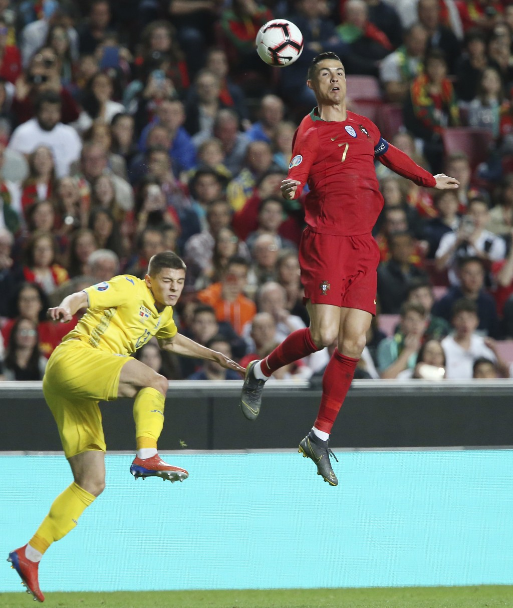 Portugal's Cristiano Ronaldo, right, challenges for the ball with Ukraine's Vitaliy Mykolenko during the Euro 2020 group B qualifying soccer match bet...