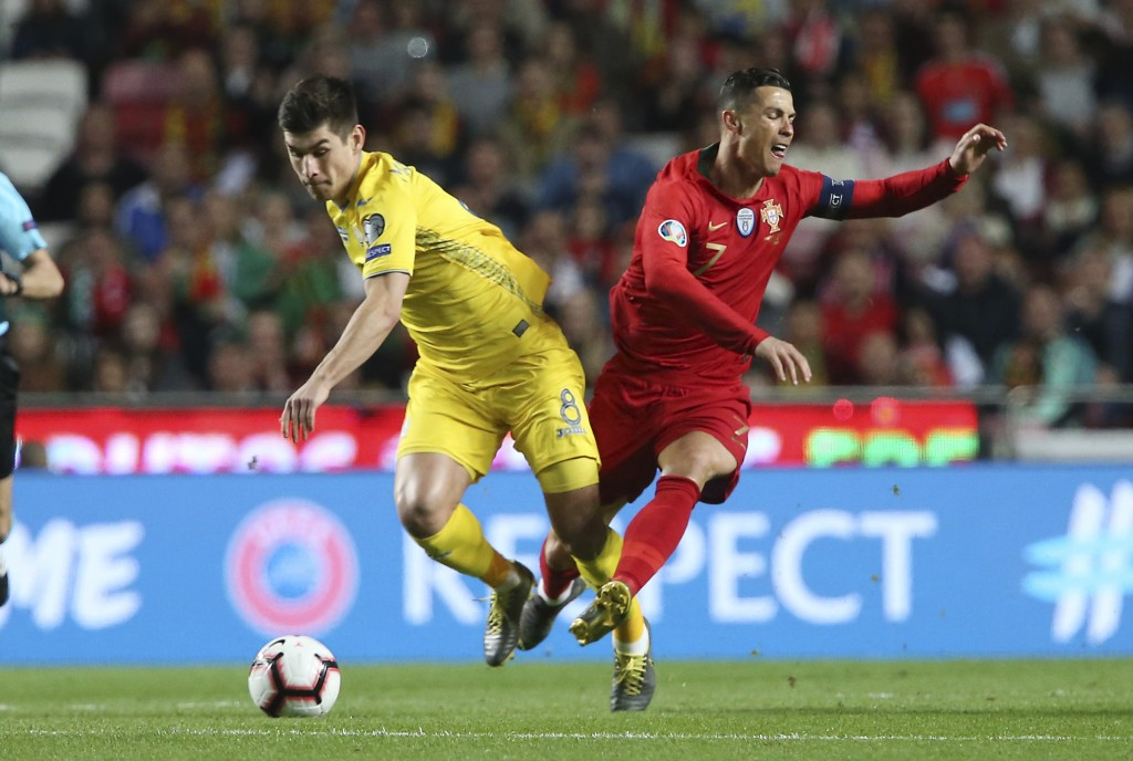 Portugal's Cristiano Ronaldo, right, challenges for the ball with Ukraine's Ruslan Malinovskyi during the Euro 2020 group B qualifying soccer match be...