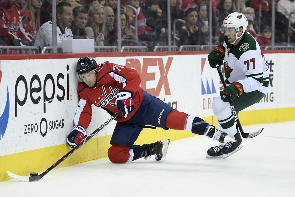 Washington Capitals center Travis Boyd (72) crashes into the boards next to Minnesota Wild defenseman Brad Hunt (77) during the second period of an NH...