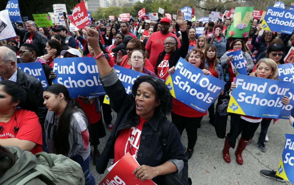 In this March 11, 2019 photo, Adrianne Bell, front center, of Houston, joins other educators during a rally to support funding for public schools in T...