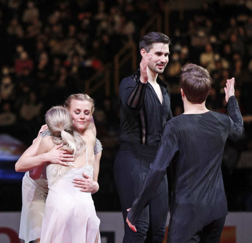 Russia's Victoria Sinitsina and Nikita Katsalapov, back to camera, greet Madison Hubbell and Zachary Donohue of the U.S. during the medal ceremony for