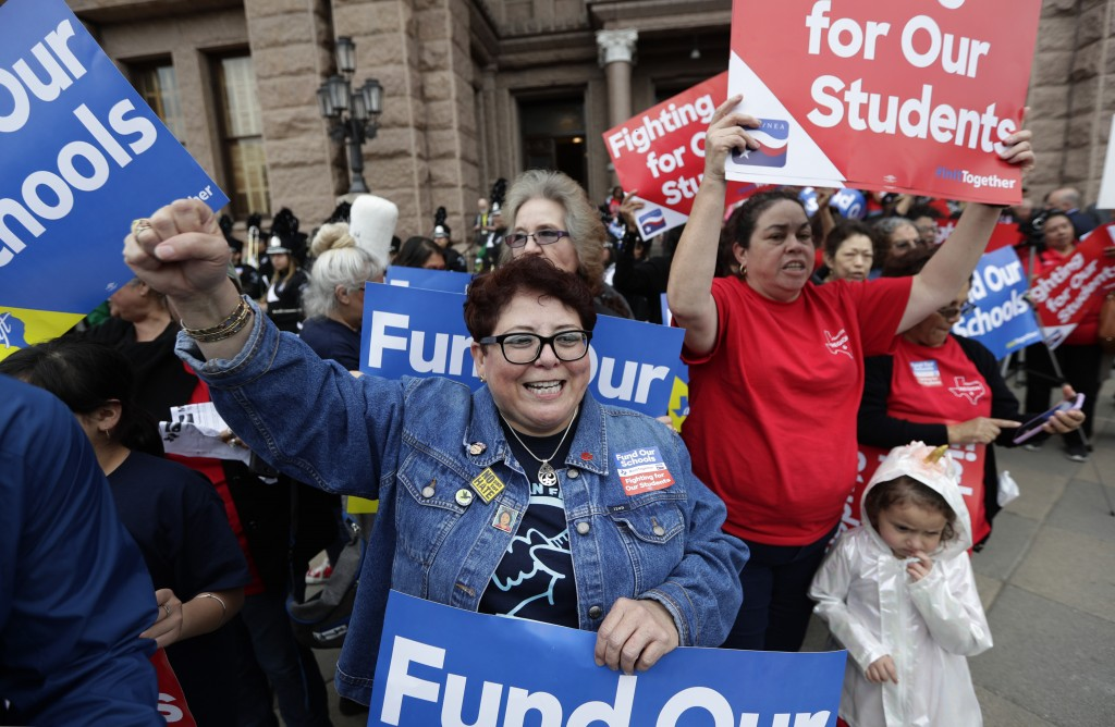 In this March 11, 2019, photo, Dr. Nancy Vera, center, of Corpus Christi, Texas, joins other educators during a rally to support funding for public sc...