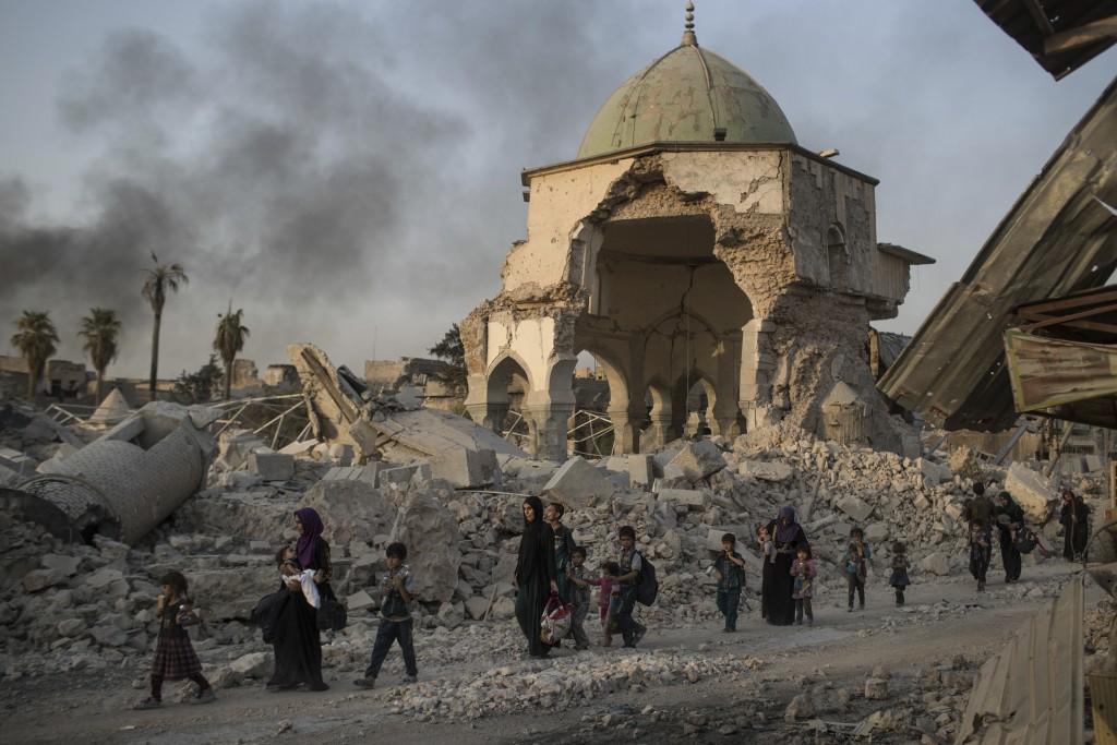 2017年美聯社檔案照,伊拉克民眾在戰煙中途經遭IS惡意毀壞的清真寺。