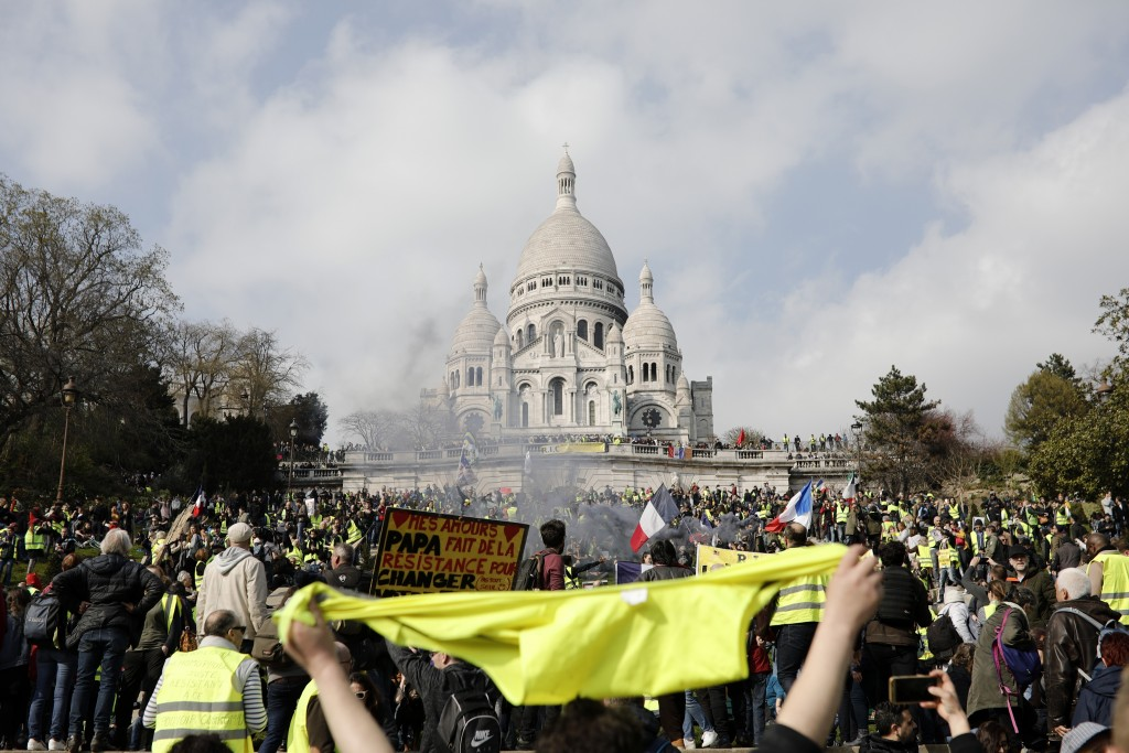 Protesters take part in a rally under the Basilica of Sacre Coeur in Montmartre, Paris Saturday, March 23, 2019. The French government vowed to streng