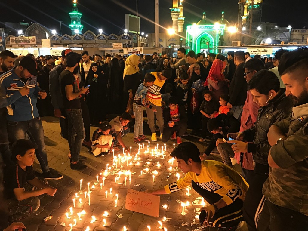 Shiite Muslim worshippers light candles as they pray for the victims of a sunken ferry, outside the golden-domed Shiite shrine of Imam Moussa al-Kadhi