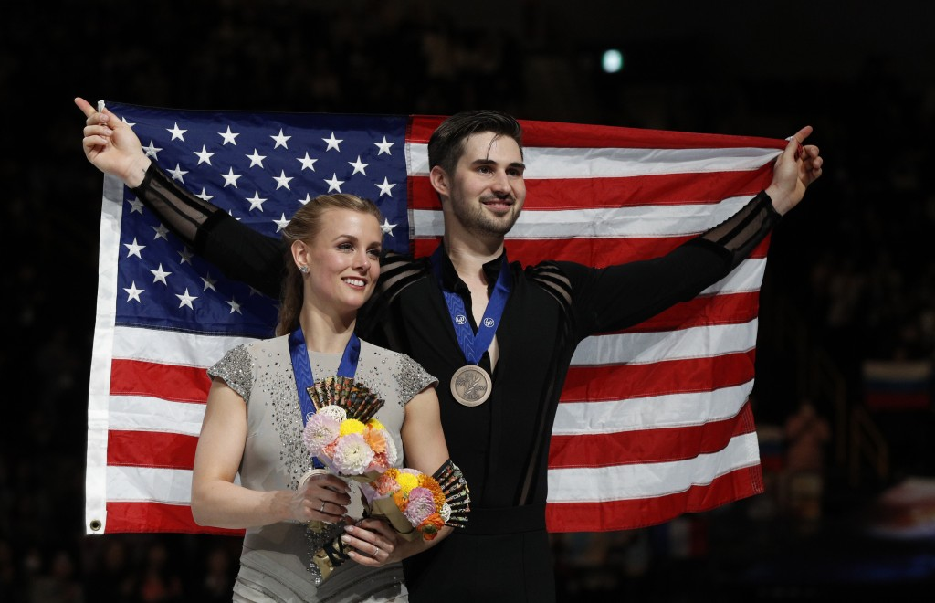 Madison Hubbell and Zachary Donohue of the U.S. stand with their national flag after winning the bronze medals for the ice dance free dance during the