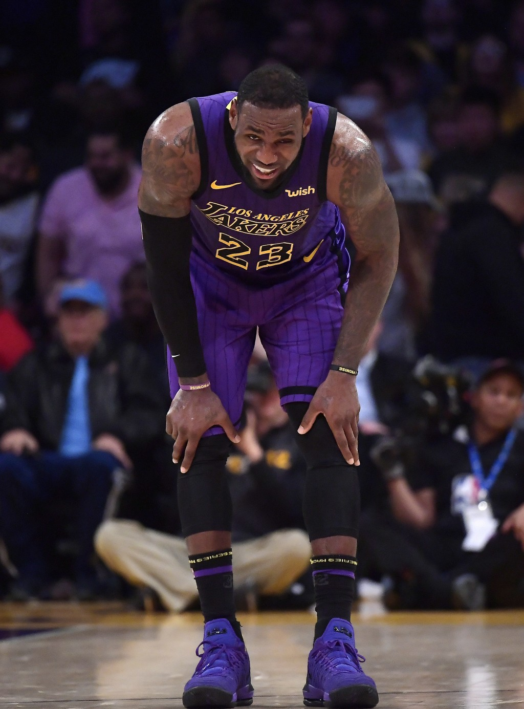 Los Angeles Lakers forward LeBron James winces after falling during the second half of an NBA basketball game against the Brooklyn Nets Friday, March ...