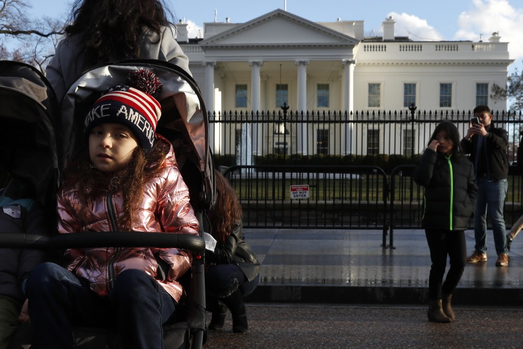 Tourists visit the White House with her family, Friday March 22, 2019, in Washington, as news breaks that special counsel Robert Mueller has concluded...
