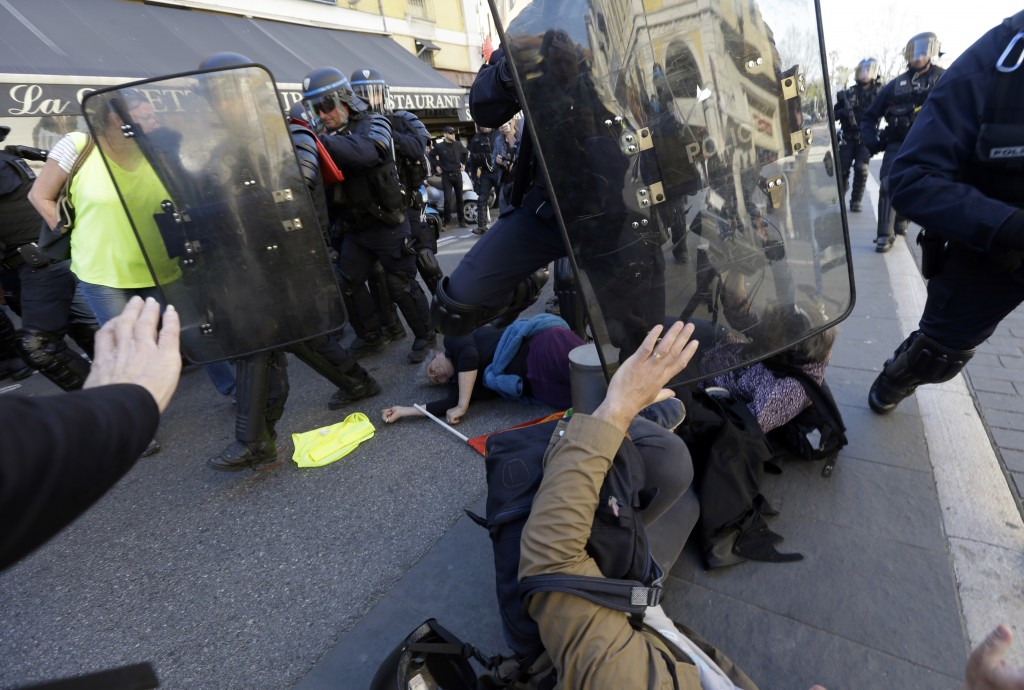 Police officers push demonstrators during a protest in Nice, southeastern France, Saturday, March 23, 2019. The French government vowed to strengthen