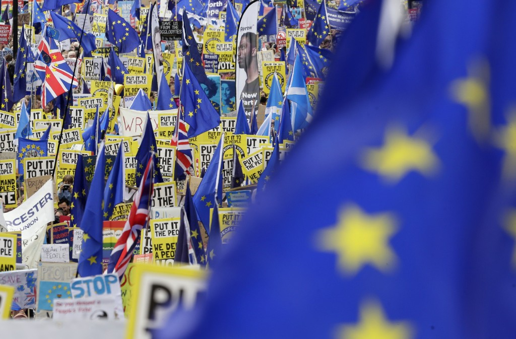Demonstrators carry posters and flags during a Peoples Vote anti-Brexit march in London, Saturday, March 23, 2019. The march, organized by the People'