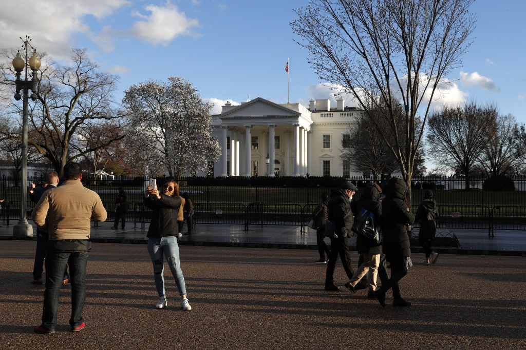 Tourists stand on Pennsylvania Avenue by the White House at sunset, Friday March 22, 2019, in Washington, after the news that special counsel Robert M...