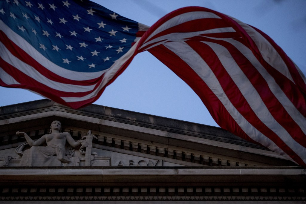 An American flag flies outside the Department of Justice in Washington, Friday, March 22, 2019. Special counsel Robert Mueller has concluded his inves