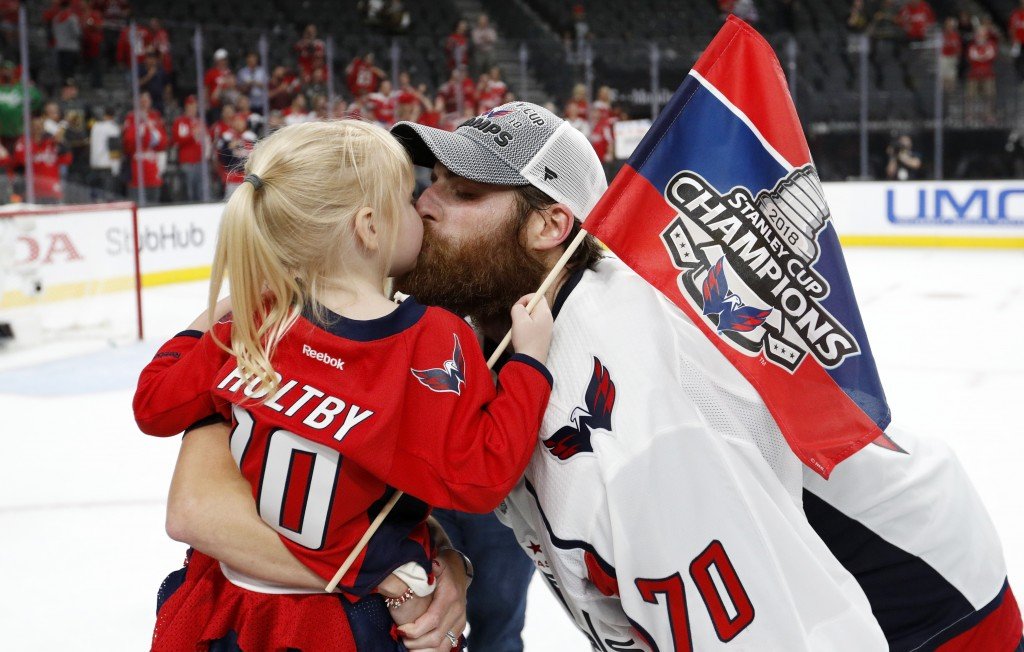 FILE - In this June 7, 2018, file photo, Washington Capitals goaltender Braden Holtby, right, kisses his daughter Belle after the Capitals defeated th