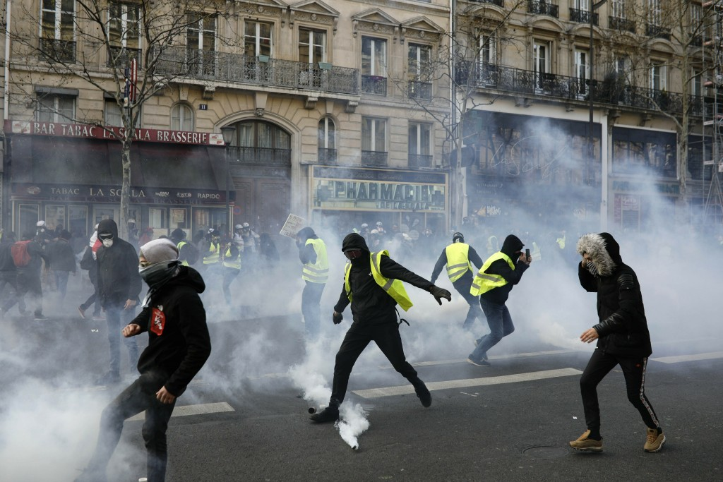 Teargas is used to disperse demonstratos during minor clashes with police in Paris, Saturday, March 23, 2019. The French government vowed to strengthe