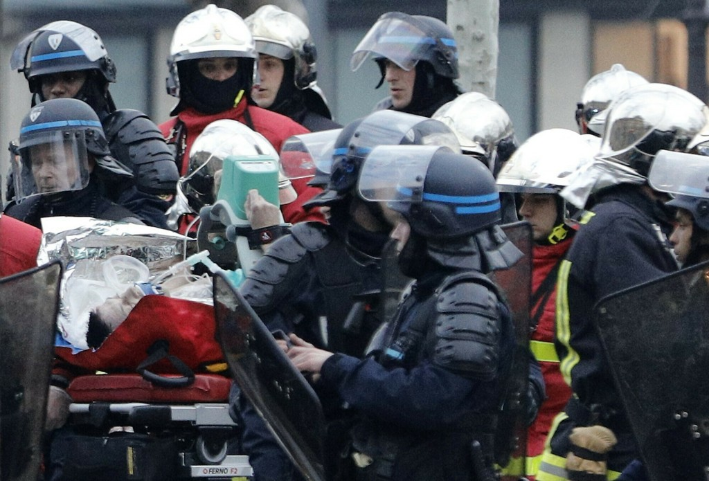 A police officer is taken away on a stretcher after falling ill while policing a demonstration in Paris, Saturday, March 23, 2019. Paris police say th