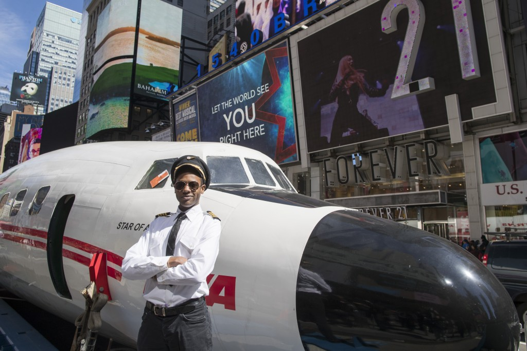 "An actor dressed as a pilot from the 1960s and 70s poses for a photo next to a Lockheed Constellation L-1649A Starliner, known as the ""Connie, is park"