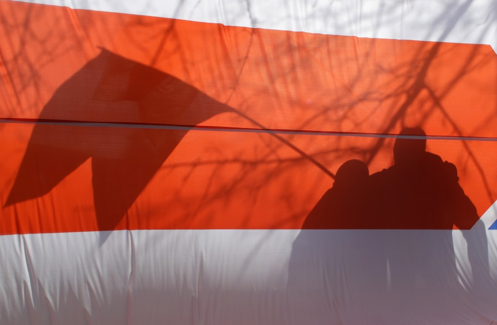 People cast shadows on opposition flag during celebration in Minsk, Belarus, Sunday, March 24, 2019, on the eve of March 25, a traditional day of demo