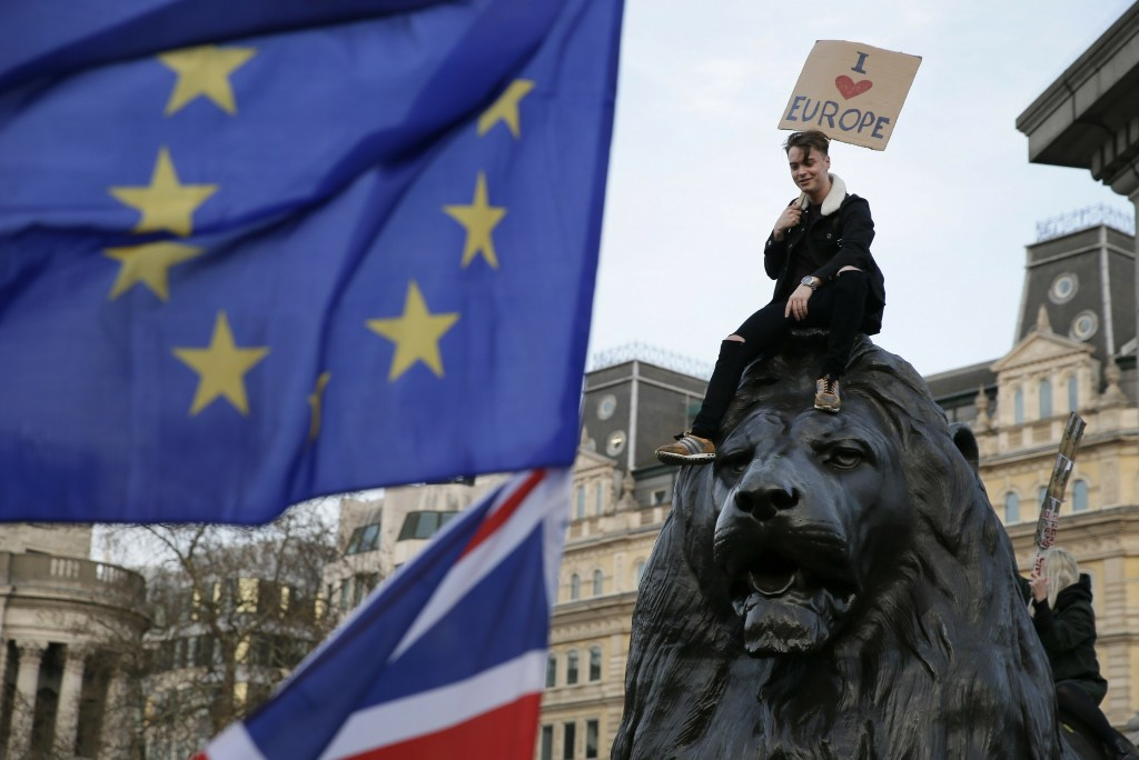 A demonstrator sits on one of the lions in Trafalgar Square during a Peoples Vote anti-Brexit march in London, Saturday, March 23, 2019. The march, or