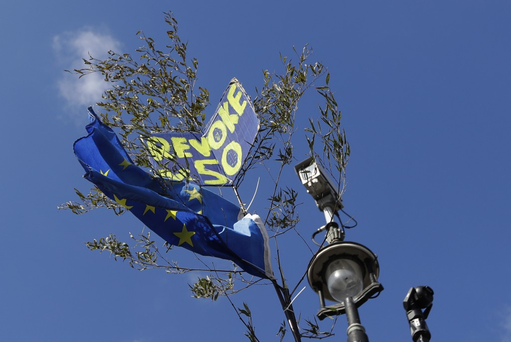 A European Union flag and a banner are caught in a tree alongside a CCTV camera in London, Monday, March 25, 2019. British Prime Minister Theresa May