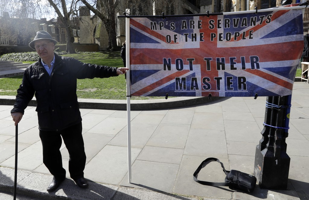 A campaigner holds a banner outside Parliament in London, Monday, March 25, 2019. British Prime Minister Theresa May is under intense pressure Monday