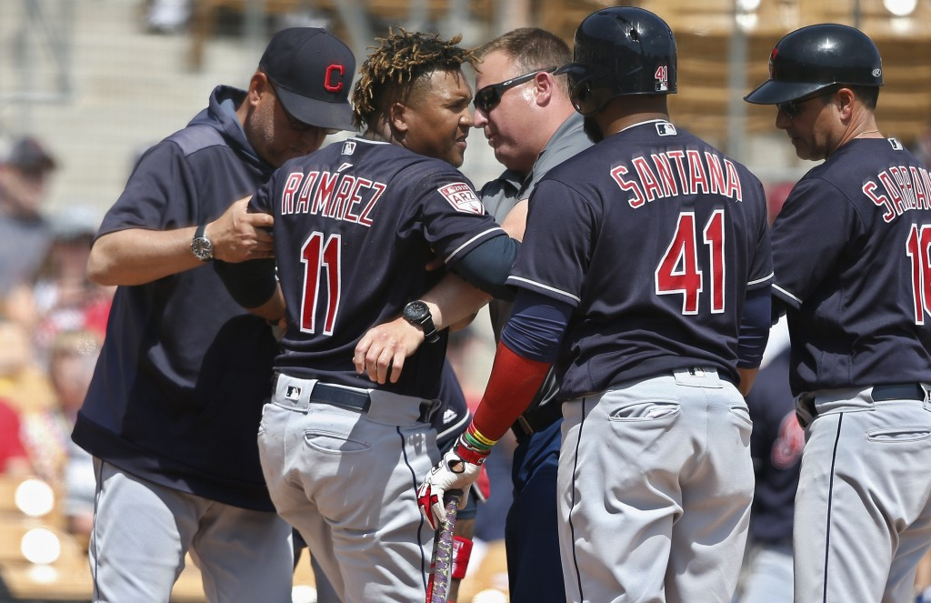Cleveland Indians' Jose Ramirez (11) is helped to his feet after an injury during the third inning of the team's spring training baseball game against...