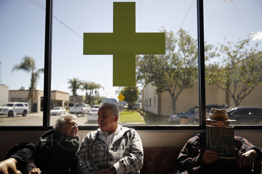 In this Feb. 19, 2019 photo, Kay Nelson, left, and Bryan Grode, retried seniors from Laguna Woods Village, chat in the lobby of Bud and Bloom cannabis