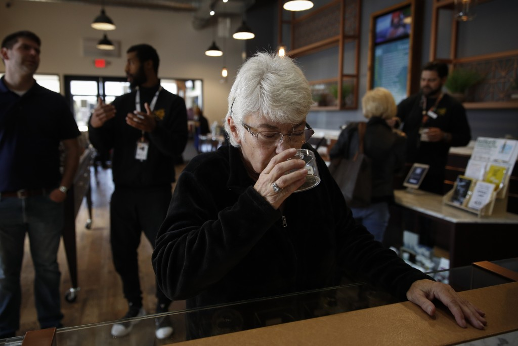 In this Feb. 19, 2019 photo, Sandy Sopher, 65, smells cannabis buds at Bud and Bloom cannabis dispensary in Santa Ana, Calif. As legal cannabis has sp