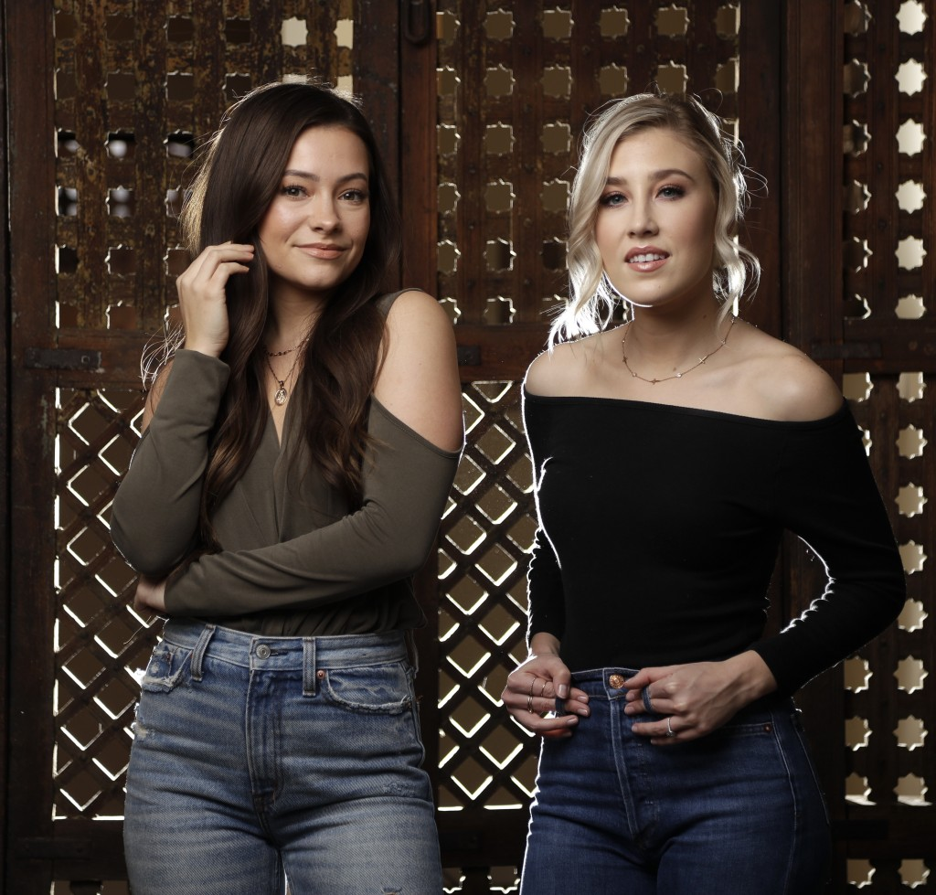 In this March 20, 2019, photo, Taylor Dye, left, and Madison Marlow, of the duo Maddie & Tae, pose in Nashville, Tenn. Nearly four years after their f...