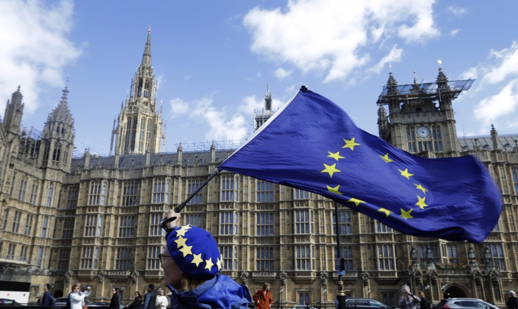 An anti Brexit campaigner shows her support for Europe waving a European Union flag outside Parliament in London, Monday, March 25, 2019.  British Pri