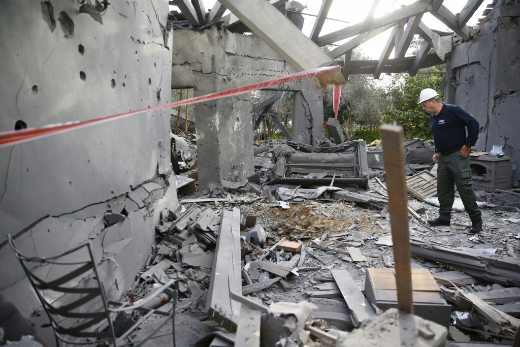A police officer inspects the damage to a house hit by a rocket in Mishmeret, central Israel, Monday, March 25, 2019. An early morning rocket from the