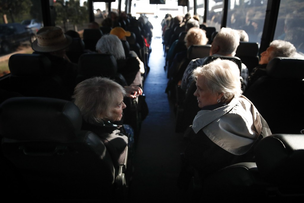 In this Feb. 19, 2019 photo, two seniors, Adele Frascella, left, and Donna Miller chat in a free shuttle bus on the way back to their retirement commu
