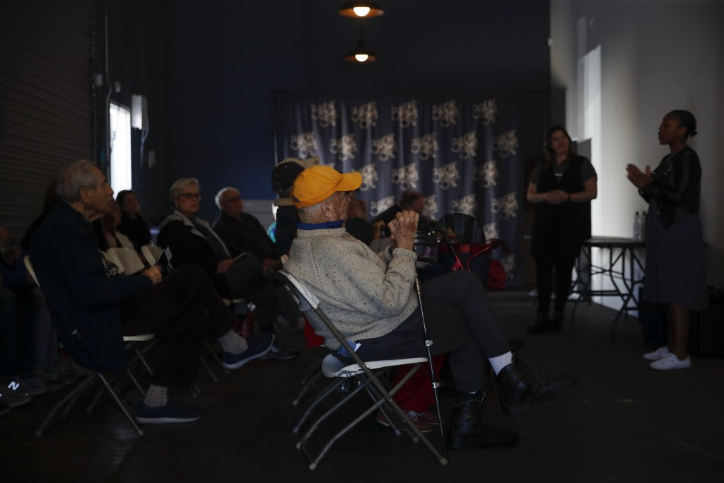 In this Feb. 19, 2019 photo, a group of seniors listen to a presentation by a cannabis product vendor at Bud and Bloom cannabis dispensary in Santa An