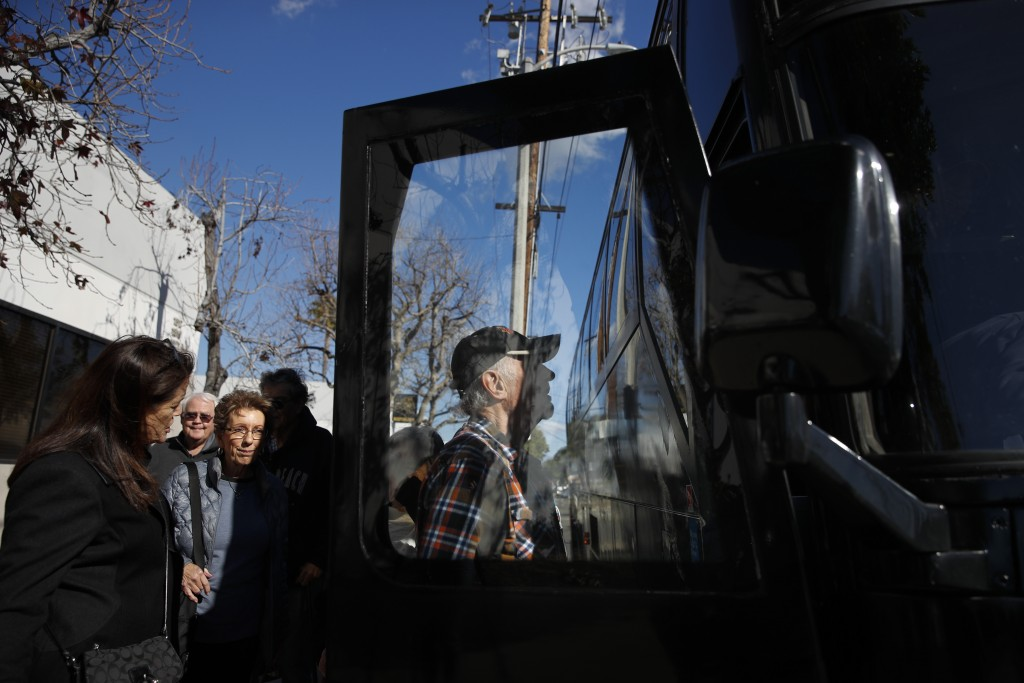 In this Feb. 19, 2019 photo, a group of seniors from Laguna Woods Village board a free shuttle bus back to their retirement community after visiting B