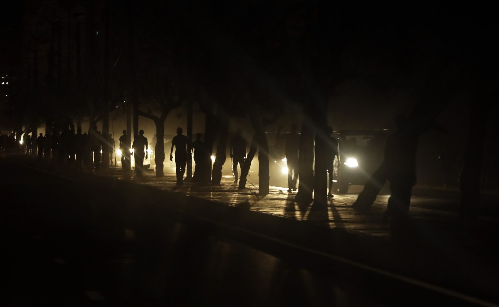 People hang out on a dark street due to damaged electricity supply in Beira, Mozambique, Monday, March 25, 2019. (AP Photo/Themba Hadebe)