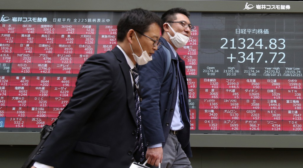 People walk by an electronic stock board of a securities firm in Tokyo, Tuesday, March 26, 2019. Asian stock prices rebounded Tuesday after global mar