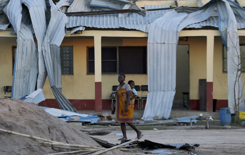 A woman carrying a baby on her back walks past damaged school in Beira, Mozambique, Monday, March 25, 2019. The United Nations is making an emergency