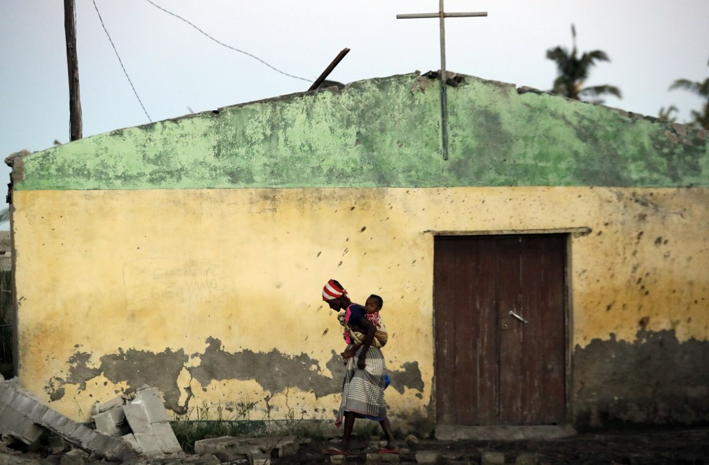 A woman carrying a baby on her back walks over a ruble of damaged houses in Beira, Mozambique, Monday, March 25, 2019. The United Nations is making an