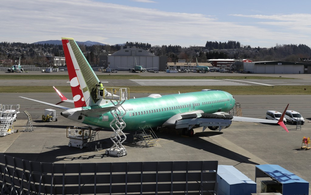 FILE- In this March 22, 2019, file photo a worker on a lift works on a Boeing 737 Max 8 being built for SpiceJet at Renton Municipal Airport in Renton