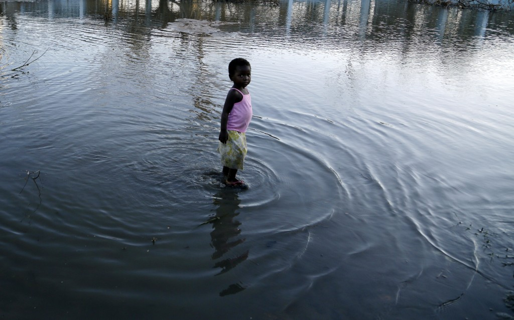 A young girl plays in the water outside a school in Beira, Mozambique, Monday, March 25, 2019. Cyclone Idai's death toll has risen above 750 in the th