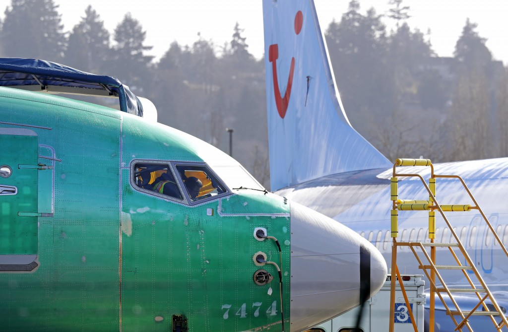 FILE- In this March 13, 2019, file photo people work in the flight deck of a Boeing 737 MAX 8 airplane being built for TUI Group parked next to anothe