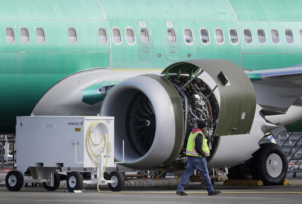 FILE- In this March 13, 2019, file photo a worker walks past an engine on a Boeing 737 MAX 8 airplane being built for American Airlines at Boeing Co.'